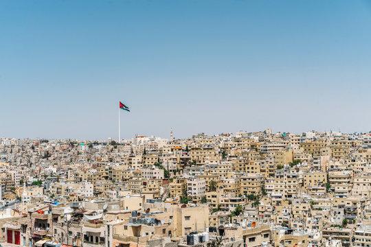Jordanian flag flying over sunny city buildings, Amman, Jordan