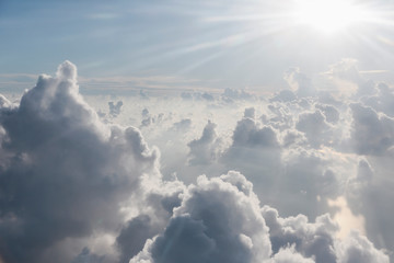 Aerial view sunbeams over fluffy clouds in sky