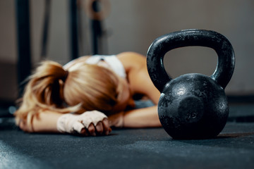 Young exhausted girl lying on a floor of fitness center after training