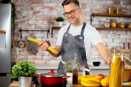 Young man cooking pasta. Chef preparing pasta in modern kitchen