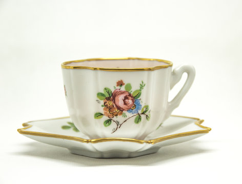 ceramic tea cup with floral paintings on a white background