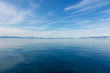 Icebergs in distance on sunny vast blue Atlantic Ocean Greenland