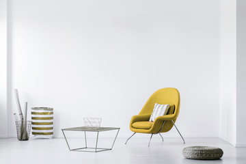 Real photo of a minimalistic living room interior with a yellow armchair. Empty, white wall. Place your poster