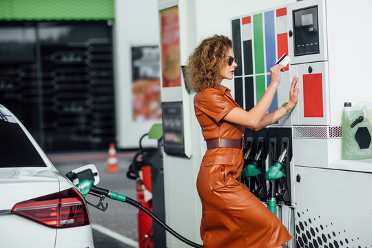 Business womanin dress refuel and pay by card.