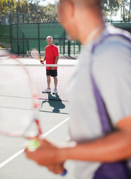 Older men playing tennis on court