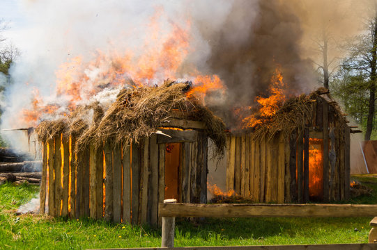 Two wooden buildings with thatched roofs burn in flames