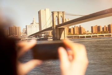 Hands taking picture of urban bridge and cityscape