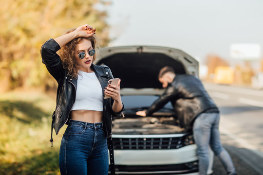Portrait of beautiful young woman using her mobile phone calls for assistance for car.