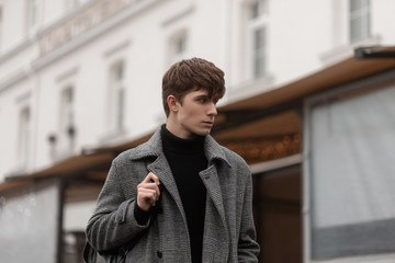 Handsome trendy young man model walks with a leather black stylish backpack in a gray checkered coat around the city. Attractive guy with a fashionable hairstyle on the street. Youth European style.