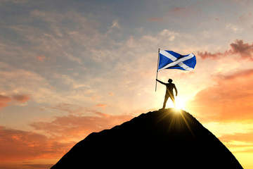 Scottish flag being waved at the top of a mountain summit. 3D Rendering