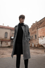 Pretty elegant young man with a fashionable hairstyle in a stylish gray plaid coat in jeans in a black vintage sweater stands outdoors on the street among the buildings. Handsome trendy european guy.