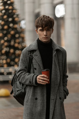 Cute European young man in a gray stylish checkered coat with a fashionable backpack stands on the street on the background of a New Year tree with a red cup of tea. Handsome modern guy model outdoors