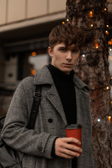 Portrait of a stylish young man in a checkered trendy coat with a cup with tea on the background of a modern building with vintage garlands. Handsome guy is enjoys the New Year holidays in the city.