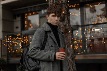 Urban young man fashion model in stylish winter outerwear walks along the street with hot tasty coffee near vintage buildings decorated with New Year lights. Modern fashion guy walks around the city.