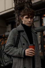 Handsome young man in a stylish plaid coat with a fashionable backpack stands with a cup of delicious coffee on the street. Attractive guy walks around the city on a festive weekend with a hot drink.
