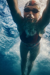 Professional swimmer moving fast in ocean water broght blue color on background, underwater shot