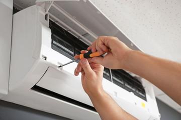Male technician repairing air conditioner indoors, closeup