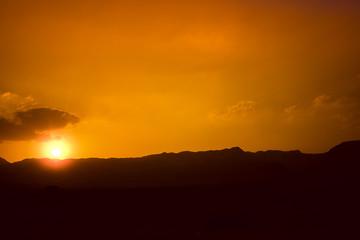 Fototapete - Mountainous desert with an orange sky. Judean desert in Israel at sunset