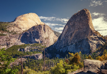 Impressive granite faces of Liberty Cap and Half Dome tower over the Mist Trail at Yosemite National Park California's Sierra Nevada mountains