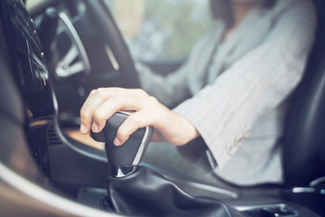 Asian Chinese Thai Business women driving to work, hand shifting the gear stick, She smiling and enjoying life in a car and hand is about to drive into the pedal shift on road for travel