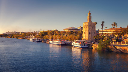 Torre del Oro (Tower of Gold), with sunset lights, on the Guadalquivir riverbed, Seville, Spain
