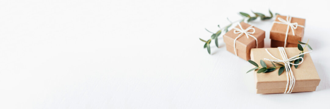 Craft gift boxes on white wooden background. Copy space for text. Eco concept