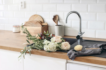 Closeup of kitchen interior. White brick wall, metro tiles, wooden countertops with kitchen utensils. Roses flowers in black sink. Modern scandinavian design. Home staging, cleaning concept.