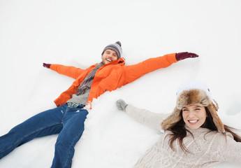 Portrait of happy couple making snow angels