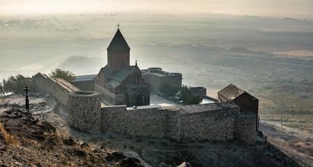 Obraz Khor Virap an Armenian monastery located in the Ararat plain in Armenia, near the closed border with Turkey, panoramic view during autumn sunrise with fog on background - fototapety do salonu