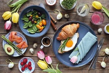 Easter festive brunch or breakfast set, meal variety with fried egg, asparagus, smoked salmon, salad bowl, avocado, croissant and smoothie. Flat layot
