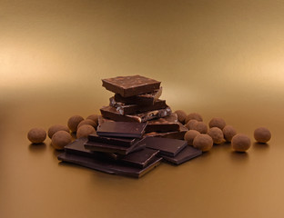 Assorted chocolate candies stock images. Chocolate sweets stock images. Pile of Chocolate stock images. Luxury chocolate isolated on a golden background