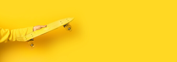 hand holding yellow  skate board over yellow background, panoramic mock up image