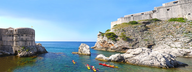 Panoramic view City Wall of Old town at Dubrovnik, Croatia.  Colorful Kayaks at Kolorina beach on a sunny day. Unrecognizable Kayakers.