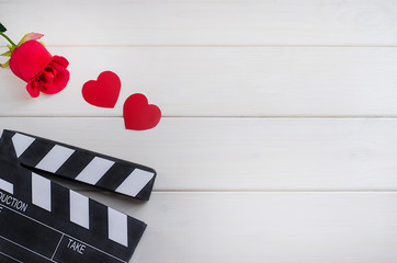 Cinema on Valentine's Day. Movie advertisement. Cinema clapper board with hearts and a rose on a white wooden background.