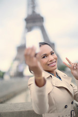 Woman taking picture in front of Eiffel Tower, Paris, France