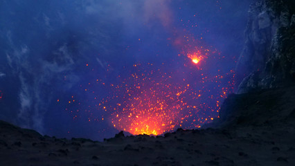 Papiers peints Bleu nuit CLOSE UP: Active volcano in the Pacific spewing out the glowing orange lava.