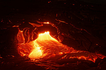 Detailed view of an active lava flow, hot magma emerges from a crack in the earth, the glowing lava appears in strong yellows and reds - Hawaii, Big Island, Kilauea volcano, Puna district, Kalapana