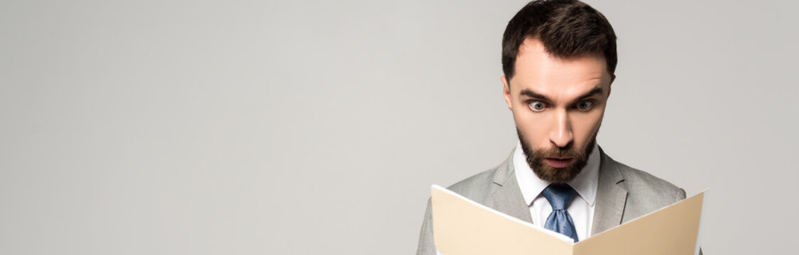 panoramic shot of shocked businessman looking at documents in paper folder isolated on grey