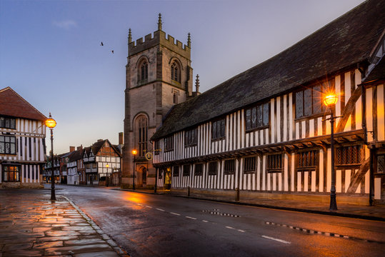 Stratford upon Avon, Guildhall and chapel with church. Street lights shine on timber framed buildings