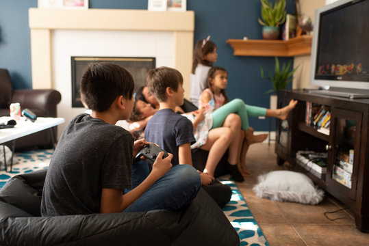Children playing video game while resting at home