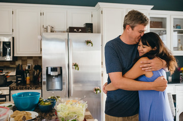 Romantic mature couple embracing while standing in kitchen at home