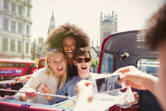 Enthusiastic friends being photographed on double-decker bus