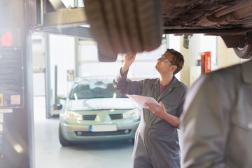 Mechanic with clipboard under car in auto repair shop