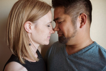 Close-up of couple romancing against wall at home