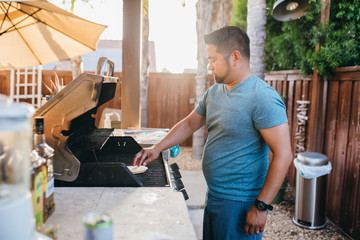 Side view of man cooking food on barbecue grill in yard