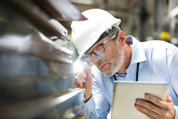 Focused engineer digital tablet flashlight examining part in factory