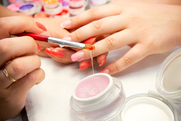 Master applies gel polish on nails in manicure salon