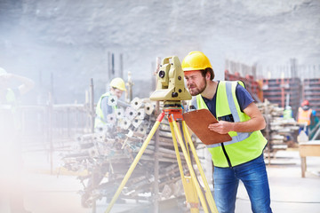 Engineer with clipboard using theodolite at construction site
