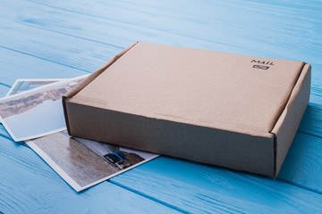 Cardboard carton box with photos, close-up. Beige package, mail sending.