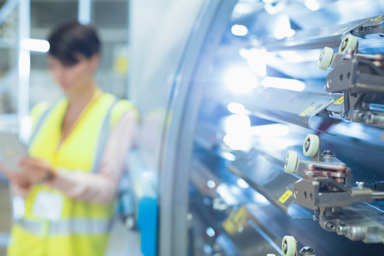 Worker behind machinery in factory
